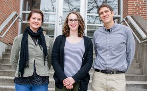 Katie Gold, Profs. Amanda Gevens and Phil Townsend standing in front of concrete stairs and glass doors in front of a brick building