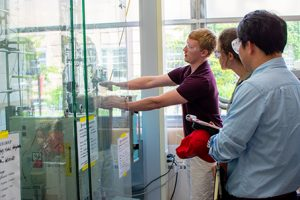 Researchers wearing eye protection work with a machine that is encased in glass