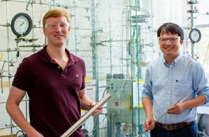 Kevin Barnett and Kefeng Huang stand in front of a reactor that is encased in glass