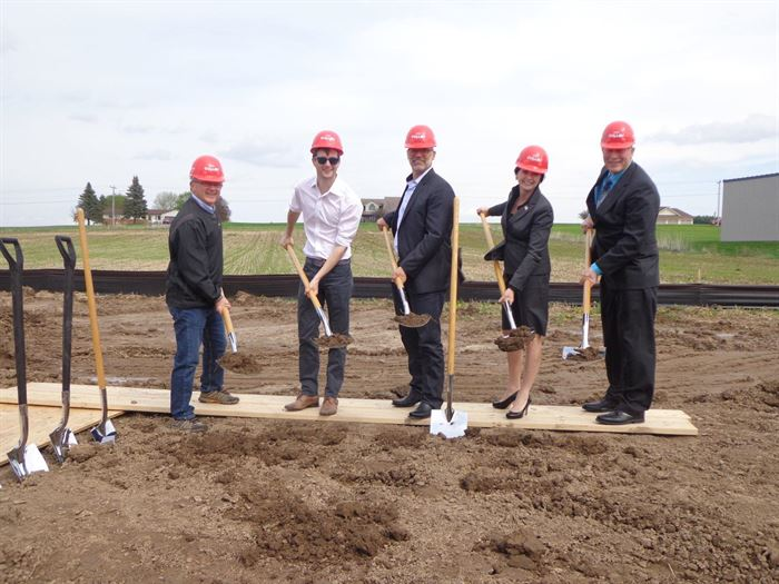 Five people in business attire with hardhats and shovels digging