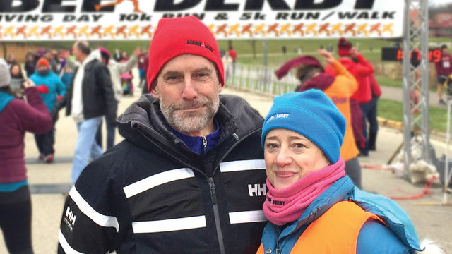 Man and woman standing outside at race dressed for cold weather hats and jackets