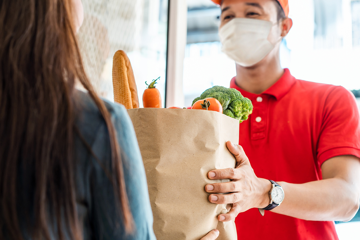 Asian delivery man wearing face mask in red uniform handling bag of food, fruit, vegetable give to female costumer in front of the house