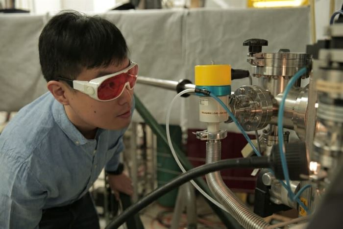 Hyungwoo Lee looks inside a thin film deposition system