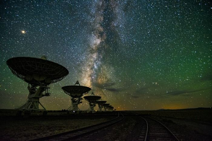 Large satellites silhouetted against a starry sky