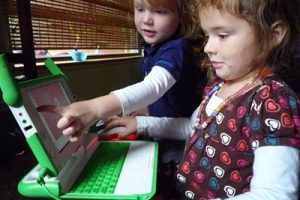 Two small kids playing on a computer