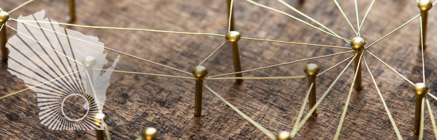 Closeup of small pins nailed to a piece of wood with string attached to, and linking, some of the pins