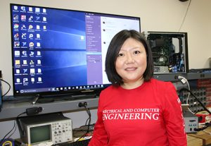 Jing Li standing in front of monitor and computer equipment