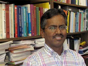 Sundaram Gunasekaran standing in front of a full bookcase