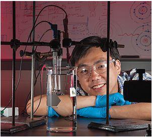 Xudong Wang resting head on arms behind a beaker set