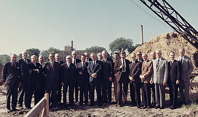 A group of people standing outside at construction sitein 1969