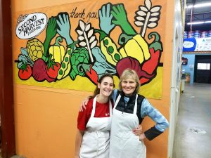 WARF Employee and her mother wearing aprons in front of wall at Second Harvest Foodbank
