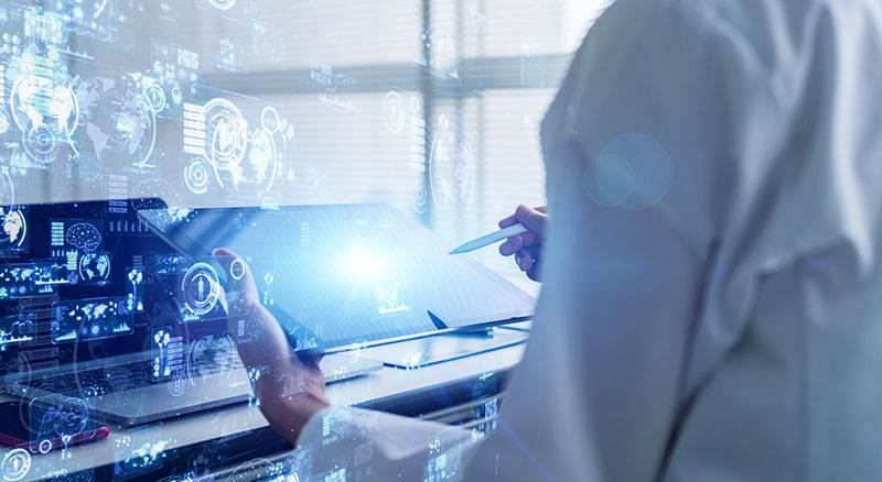 Person in lab coat using futuristic technology and a tablet